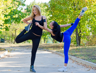 Two young women exercising in a park