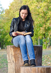 Woman sitting on a tree stump reading