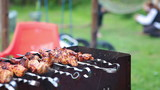 Skewers on grill and unrecognizable mother and kid playing poster