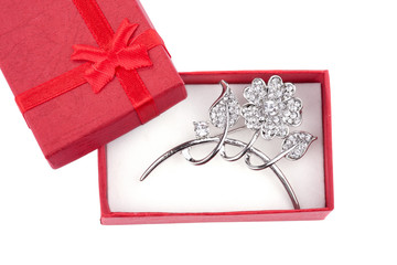 Beautiful silver brooch in a red gift box, isolated on white