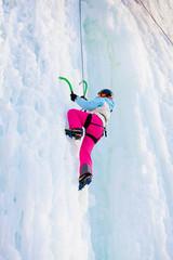Woman climbing frozen waterfall