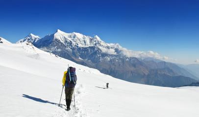 Lonely trekkers on big snow fieldsin Himalaya