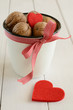 Walnuts in white cup and two red hearts