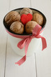 Walnuts in white cup bounded up in red ribbon and bow