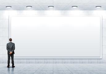 Business person standing near a blank billboard
