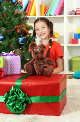 Little girl with large gift box near christmas tree