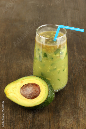 Useful fresh avocado and half avocado on wooden table close-up