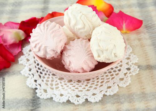 Marshmallows on color plate on light background