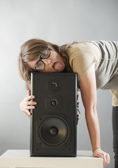 Beautiful woman laying on the big wooden speaker