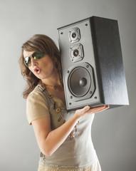 Beautiful woman holding big wooden speaker