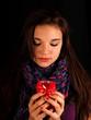 Mädchen mit Schal schaut auf Kerze