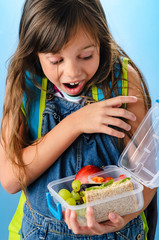 Cute school girl is excited looking into her healthy lunchbox