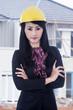 Beautiful engineer standing outdoor with yellow helmet
