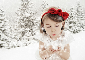 Three years old girl blowing smowflakes in winter landscape