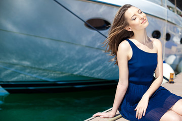 beautiful brunette woman relaxing on dock near the boat