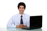 Happy office worker sat at his desk smiling