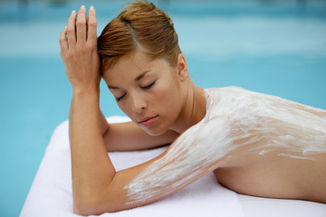 Woman laid on massage table with cream on her back