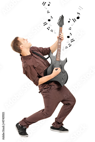 Full length portrait of a rock star playing on a guitar