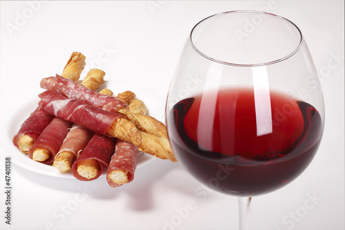 Glass of red wine and biscuits with bacon