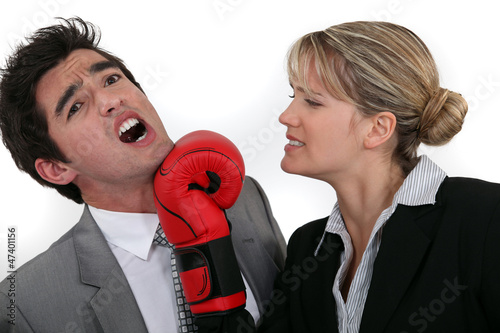 businesswoman hitting a man with a boxing glove