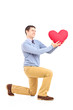 Smiling male kneeling with red heart shape object