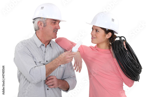 electricians talking and holding a bulb and a wire