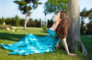 beautiful woman in blue dress in park on green meadow