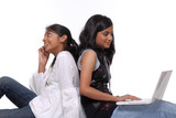 Two girls using laptop and mobile phone