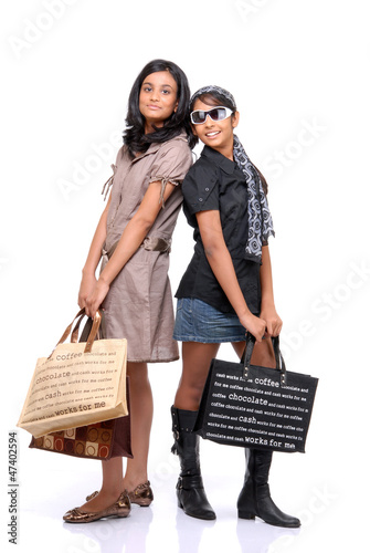 Happy young friends standing with shopping bags