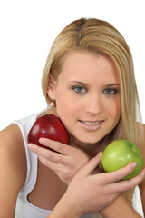 Young blonde woman with a red and a green apple
