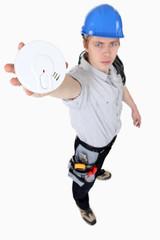 Builder holding smoke alarm
