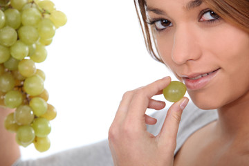Woman eating green grapes