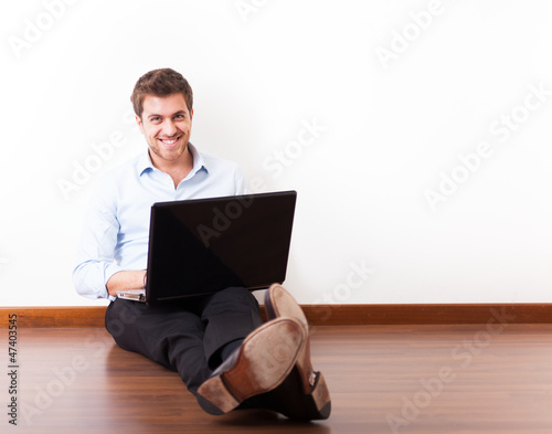 Young man using a laptop on the floor
