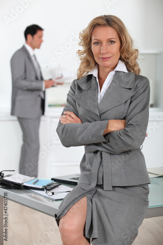 Businesswoman sitting on desk