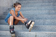 girl sitting on the stairs and puts on skates