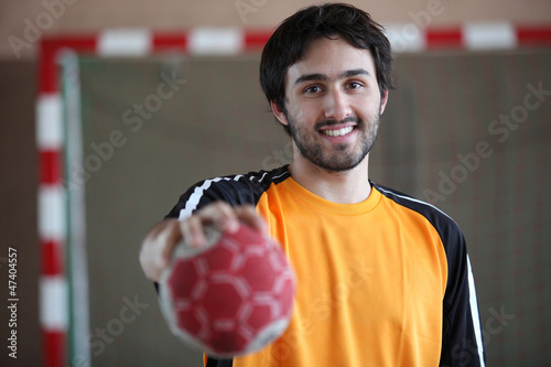 portrait of young handball player holding out ball