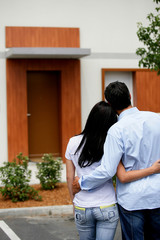 Young couple embraced face to a house