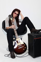 Serious woman with electric guitar