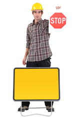 Young bricklayer holding stop sign
