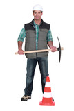 Man with pick-axe and traffic cone