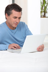 Man using laptop on his bed