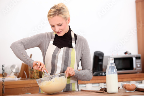 blonde woman making a cake