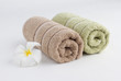 Towels rolled up and flower on white background