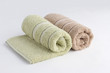 Green and brown towels rolled up on white background