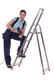 female craftsman with drill and ladder