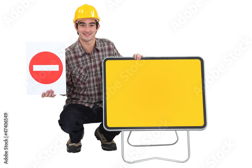 Traffic worker kneeling by road signs