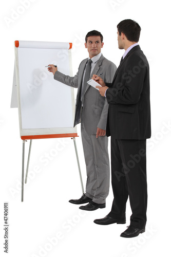 Businessmen standing at a flipchart