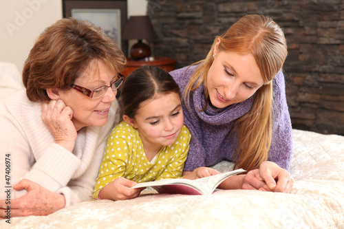 Three generations reading a book together