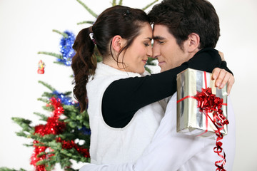 Couple kissing by a Christmas tree