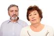 Portrait of senior couple, focus on woman, isolated